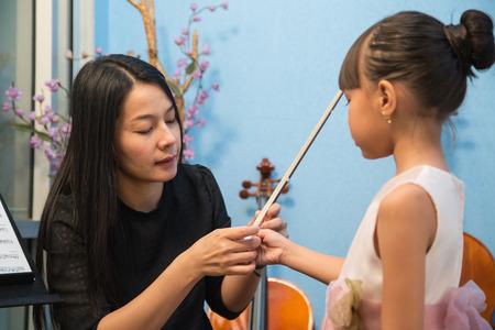 violinista: violinist playing violin musics and children in studio school. Foto de archivo