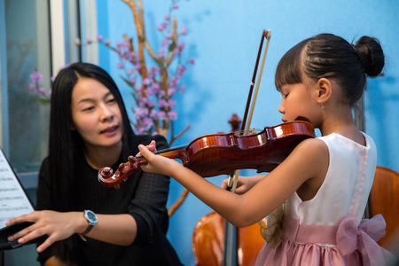 violin player: Violinist teacher teach student with violin in studio school.