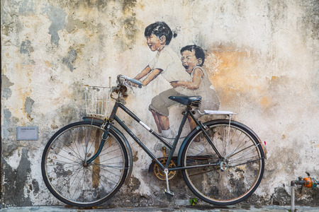 GEORGE TOWN,PENANG ,MALAYSIA- CIRCA March 26, 2015: Public street art Name Children on a bicycle painted 3D on the wall that's two little  Chinese girls riding bicycle.  in Georgetown, Penang, Malaysia. Redactioneel