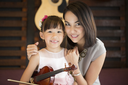 mam: Mam and daughter portrait with  violin in studio school.