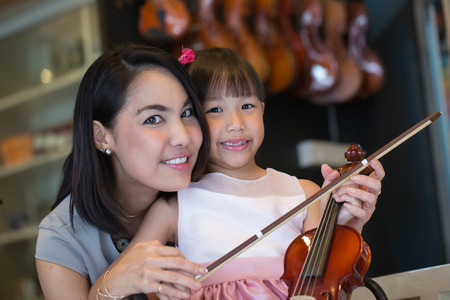 mam: Mam and daughter portrait with violin in studio school. Stock Photo