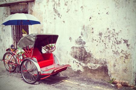 trishaw: Old Red Trishaw stop beside vintage.
