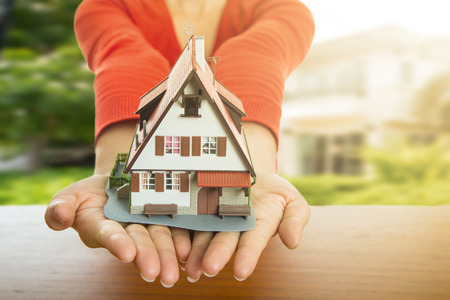 home finance: Woman show model house and real agency property. Stock Photo