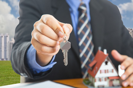 property owners: Businessman show Keys for your good property with real agency property.