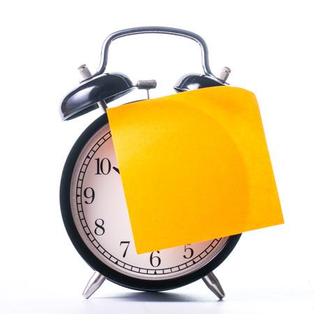 paper note: Reloj de alarma de color negro de la vendimia con la nota de papel en el fondo de escritura Foto de archivo