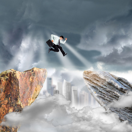 difficult lives: Businessman jump over precipice mountain rock on over blue sky. Stock Photo