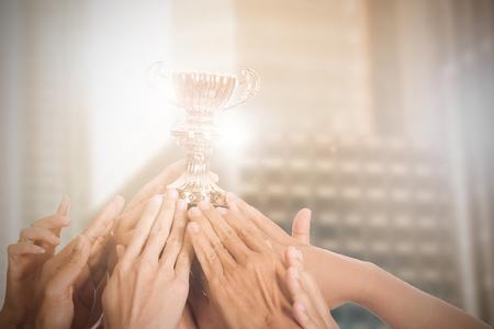 Bedrijfs succes met hun winnaar trofee houden door handen.