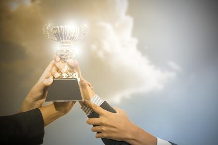 Uomini d'affari che tengono premio trofeo dopo la vittoria concorrente. Archivio Fotografico - 46906153