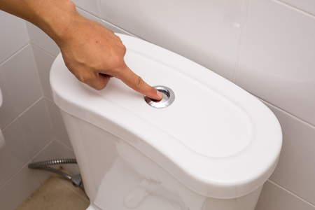 flush: Use finger flush toilet after used in washroom. Stock Photo