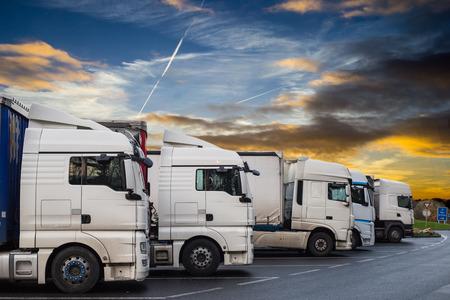 Logistieke vrachtwagens voor levering in vrachtwagens in de schemeringstijd.