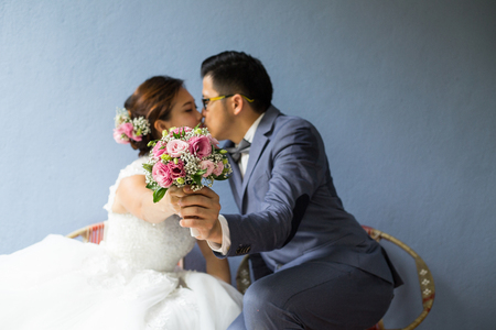 young couple kissing: Two asian people kissing behide bouquet on valentines day