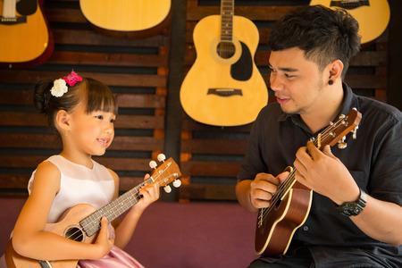 Ukulele gitaarleraar teach muziek op school