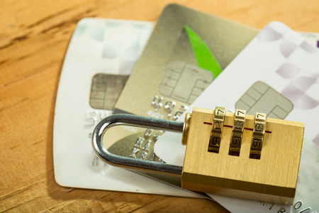 combination lock and credit cards on wood board.