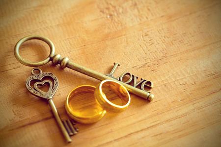 Gouden hart sleutel en verlovingsring met een houten bord.