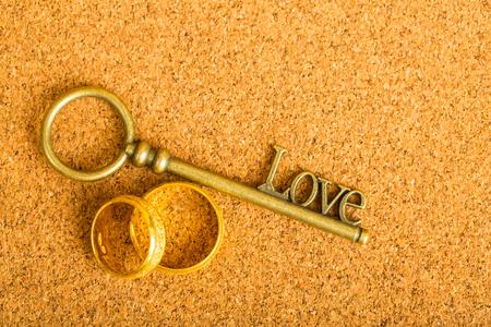 Gouden hartsleutel en verlovingsring met vintage papier. Stockfoto