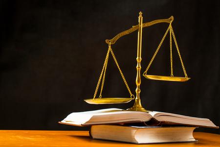 balanza de la justicia: Justicia de escala con libros sobre la mesa.