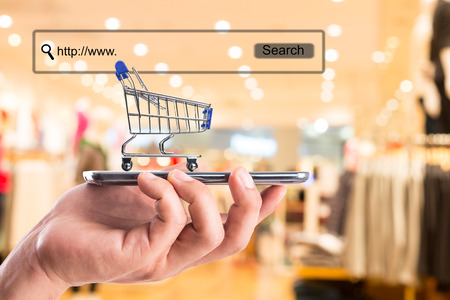 commerce: shopping cart and money with your e-commerce. Stock Photo
