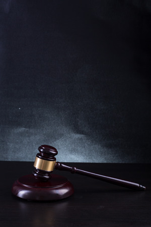 verdicts: Wooden Judges gavel with black background.