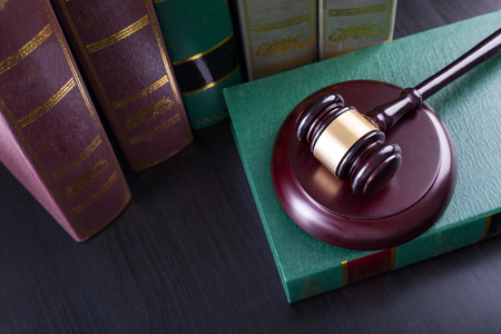 legality: Wooden Judges gavel ,golden scales justice with black background.