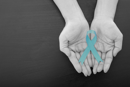 Ovarian cancer green ribbon holding by woman who need to show healthcare concept.