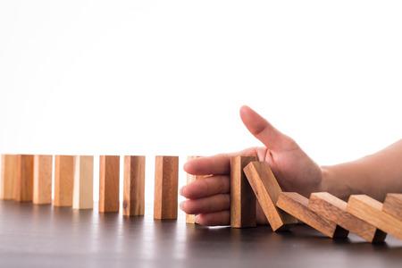 Arresti l'effetto di rischio di domino, uomo d'affari facendo uso della mano per la soluzione della gestione.
