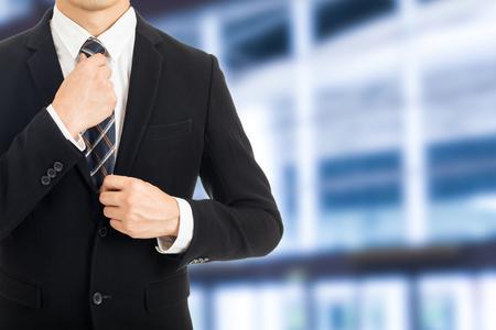 adjust: Businessman adjust necktie before start to the office.