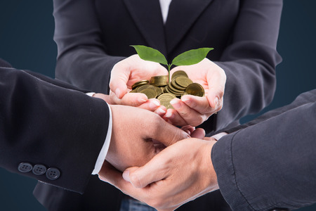 growing together: Business team holding growing money together for saving their financial to investment in the future. Stock Photo