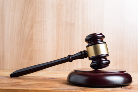 defendant: Wooden Judges gavel ,golden scales justice with black background.