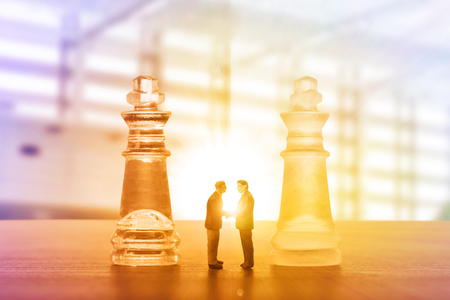 Businessman handshake for agreement with partnership to agree their business. King chess game