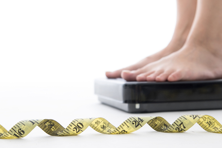 weightloss: Weight scale ,woman measure weightloss with isolated whie background.