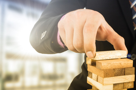 Business risk concept with wood jenga game.Businessman manage his strategy.
