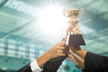 Zakenman team bedrijf award trophy voor hun overwinning tonen.