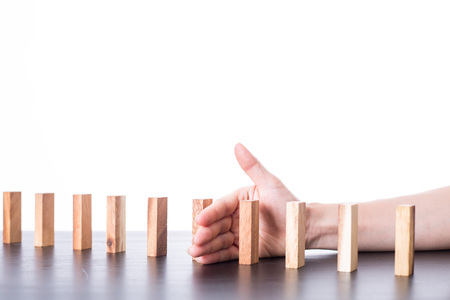 the collapsing: Stop domino risk effect ,businessman using hand for management solution.