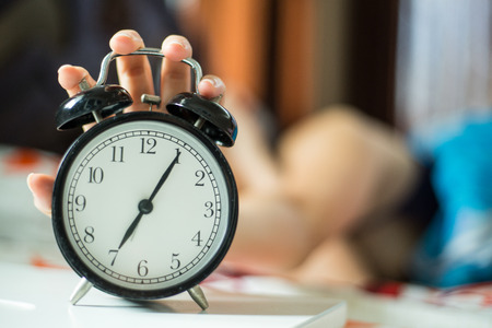 seven persons: Wake up ,woman trying to stop alarm clock in the morning.