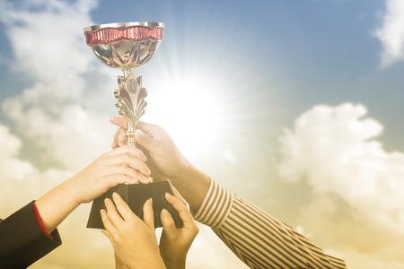 primer lugar: equipo de negocios la celebración de trofeo de premio por mostrar su victoria.