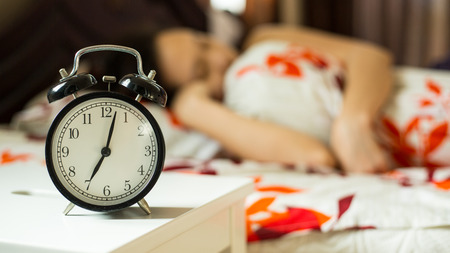 Wake up ,woman trying to stop alarm clock in the morning.