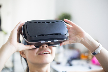Asian woman holding VR technology headset for watch reality virtual glasses at home.
