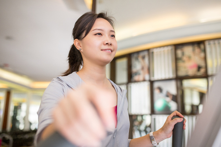 Asian woman running with machine walking in fitness room. Stock Photo