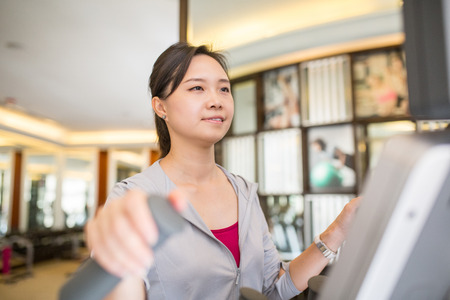 execute: Asian woman running with machine walking in fitness room. Stock Photo