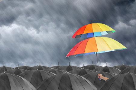 Diferente colorido espectáculo sostiene el paraguas de identificar fuera de la muchedumbre. Foto de archivo