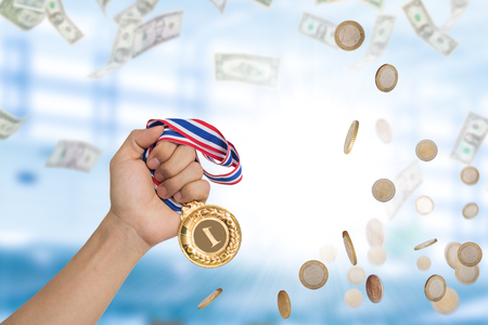 Winner business.Businessman holding golden coin after win competition market by money income to his team. 版權商用圖片