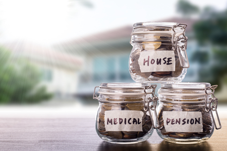 Savings money for investment ,pension ,medical and house with pinggy bank bottle. Banco de Imagens