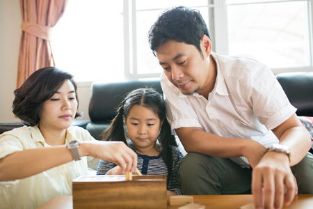 cute guy: Happy Asian family having fun playing Jenga in the living room Stock Photo