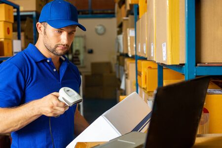 Worker using scaner for check in and check out product in warehouse