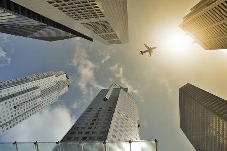 Airplane flight over modern building at afternoon. Standard-Bild