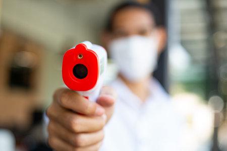 Asian male waiter holding temperature gun before entry inside restaurant.