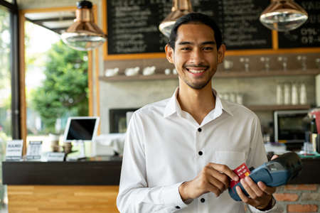 Asian male waiter holding credit card for load payment from customer.Business owerner smiling after receive money. Standard-Bild