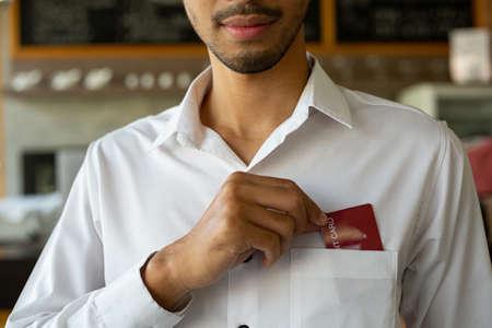 Smart Asian man pick up credit card for pocket for payment for cash money in restaurant.