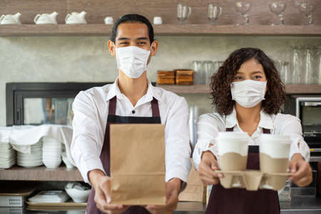 Asian barista with mask holding paper bag and coffee cup for customer take away for provent coronavirus in restaurant.