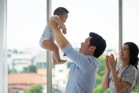 Asian family enjoy together in living room.Thai parent holding their baby for joy with lifestyle.